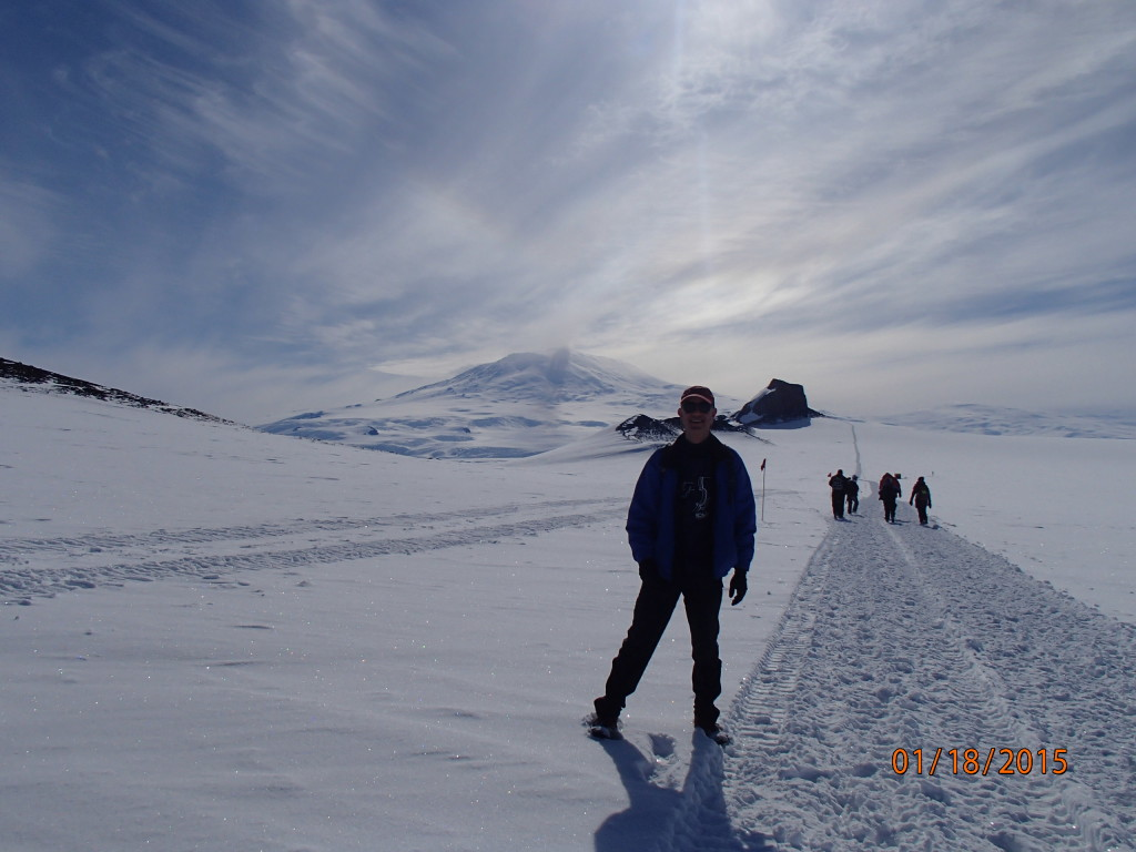 Sunny hike on the glacier to Castle Rock with Mt Erebus volcano in the distance