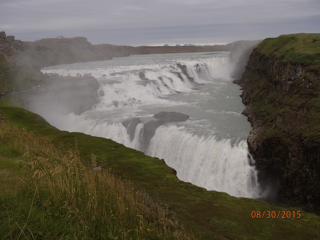 Gullfoss staggering waterfall with about a dozen people standing on the rocks in the middle left