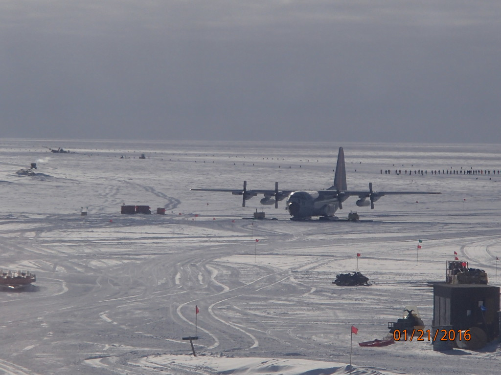 Frozen C-130 at the South Pole and disabled plane in the upper left- note the line of people walking the runway looking for debris